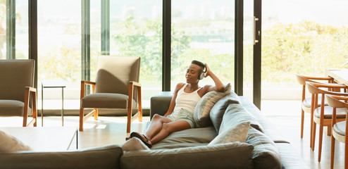 Young woman relaxing, listening to music with headphones on living room sofa