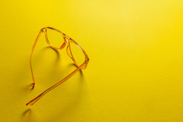 Fashionable yellow female sunglasses isolated on abstract background with copy space