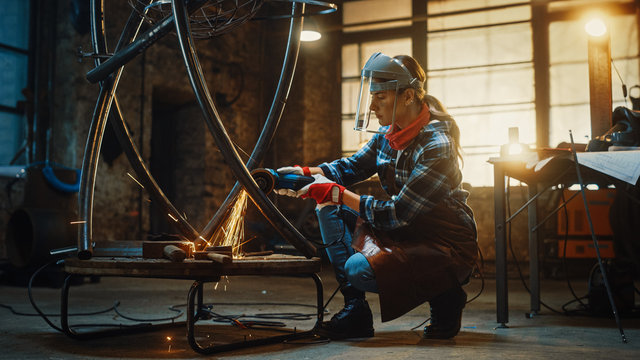 Young Contemporary Female Artist is Polishing a Metal Tube Sculpture with an Angle Grinder in a Workshop. Pretty Empowering Woman with Ear Piercing.