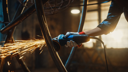 Close Up of Hands of a Metal Fabricator Wearing Safety Gloves and Grinding a Steel Tube Sculpture with an Angle Grinder in a Studio. Working with a Handheld Power Tool in a Workshop.