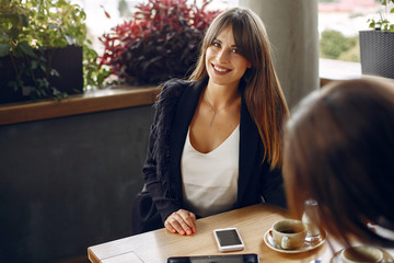 Wall Mural - Two beautiful women working. Friends in a cafe. Businesswomen talking and working with a tablet