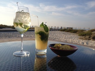 Close-up Of Drinks With Chips On Table At Beach Against Sky
