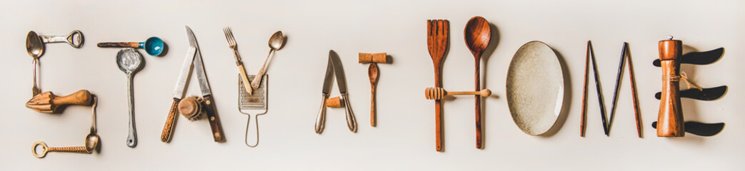 Stay at home lettering made from kitchen utensils, top view. Flat lay of stay at home words for quarantine isolation during coronavirus pandemic, wide composition. Banner for website for food shop