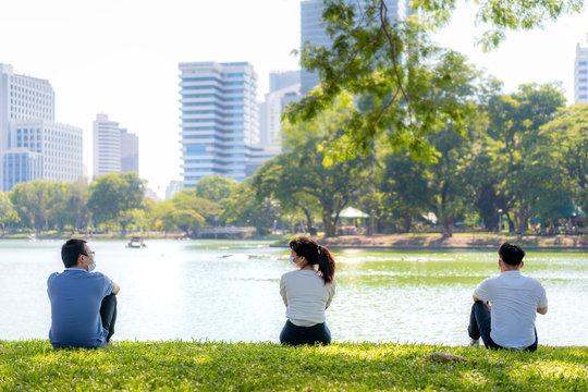 Asian young three man and woman talking and relaxing with they friend and wearing mask sitting distance of 6 feet distance protect from COVID-19 viruses for social distancing in park.