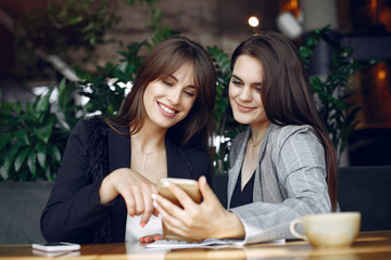 Wall Mural - Two beautiful women working. Friends in a cafe. Women use the phone