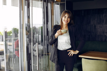 Wall Mural - Beautiful woman working. Busineswoman in a stylish clothes. Woman standing near window