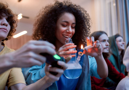 For great mood. Young afro american girl lighting marijuana in the glass bong, relaxing with friends on the sofa at home. Young people playing video games and smoking weed