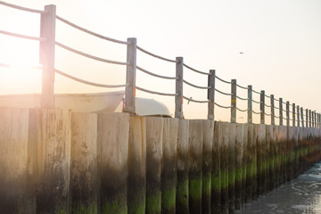 Wooden fence on the beach in Dubai. Wooden pier with boats at sunset