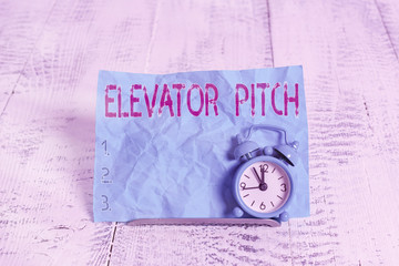 Text sign showing Elevator Pitch. Business photo showcasing A persuasive sales pitch Brief speech about the product Mini blue alarm clock stand tilted above buffer wire in front of notepaper