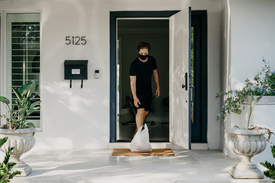Man at home with a mask receiving food delivery