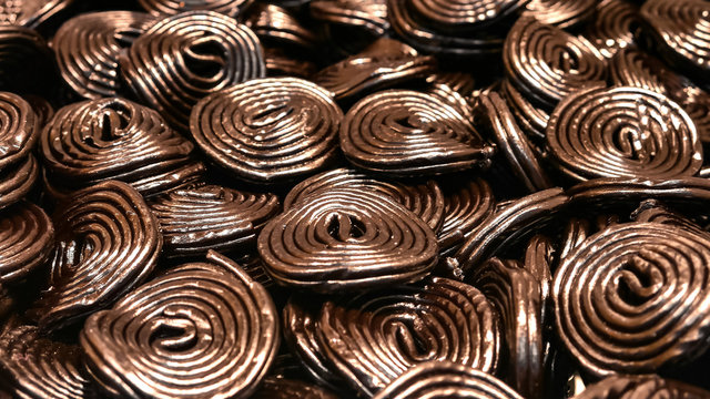 Licorice candy. Background of dark licorice sweets rolled into wheels, pastry, flavored and colored black with licorice root extract. Sweets.
