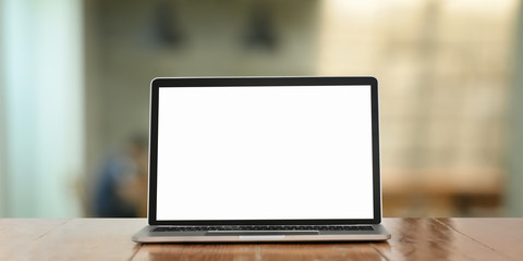 Photo of white blank screen computer laptop putting on working desk over comfortable living room as background.