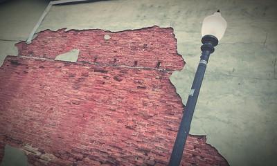 Obraz Low Angle View Of Street Light Against Weathered Brick Wall - fototapety do salonu