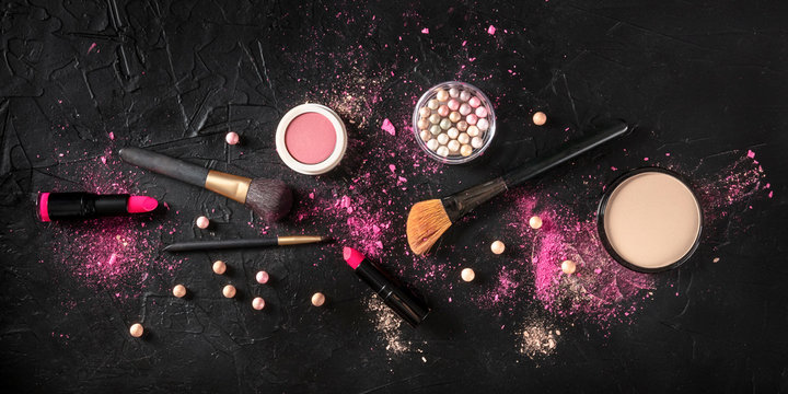Professional make-up overhead panoramic shot on a dark background. Brushes, lipstick and other products, a flat lay