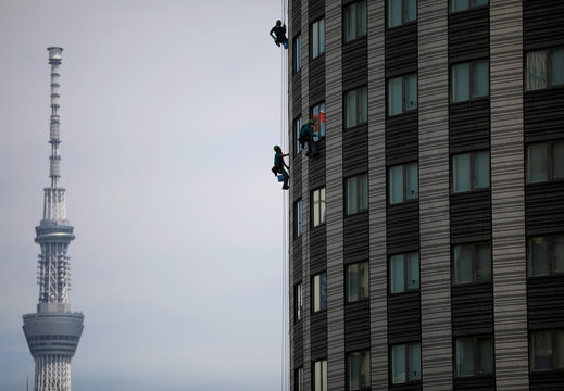 Workers clean the windows of a hotel with Tokyo Skytree, the world's tallest broadcasting tower, in the background during the spread of the coronavirus disease (COVID-19) in Tokyo