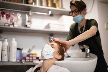 Hairdresser and customer in a salon with medical masks during virus pandemic. Working with safety...