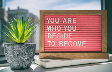 Fototapeta Inspiration quote message sign saying You are who you decide to become - life advice for self esteem, confidence. Home background. obraz