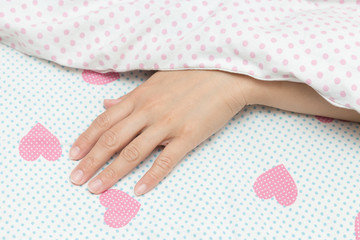 Sleeping woman finger under a white blanket top view. Beautiful fingers of a young woman on the bed.