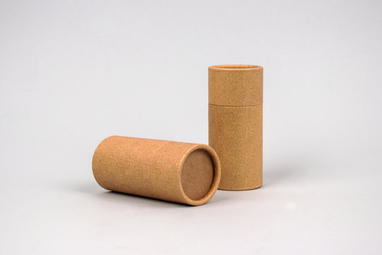 Paper tubes on grey background with copyspace - cardboard packaging for natural cosmetics and deodorant. Reusable packaging and recycling concept. Mockup