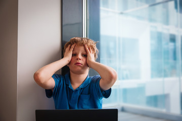 kid bored with computer at home, boy stressed and exhausted