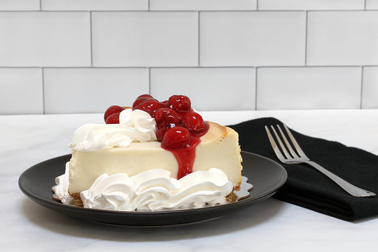 A slice of  New York style cheesecake with cherries and whipped cream.