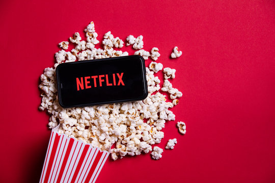 LONDON, UK - MAY 14 2020: Netflix logo on a smartphone with popcorn