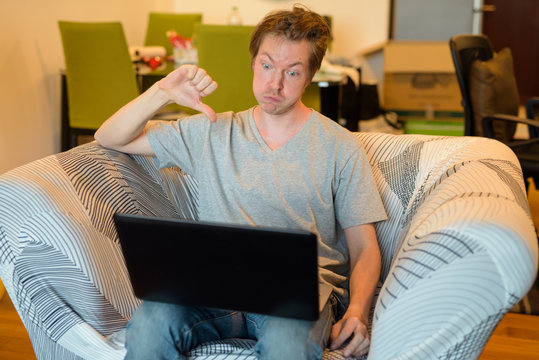 Stressed young man having online meeting with laptop while in quarantine at home