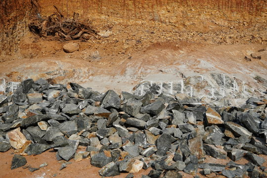 Pile Of Rocks I.E. Lithium Mining And Natural Resources Like Limestone Mining In Quarry. Natural Zeolite Rocks Are Excavated With Deforestation In Background.