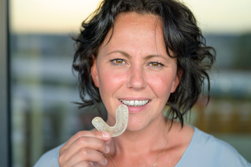 Attractive smiling woman holding a mouth guard