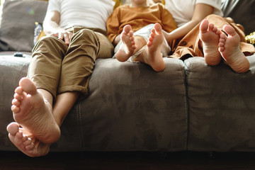 Barefoot family sitting on the sofa