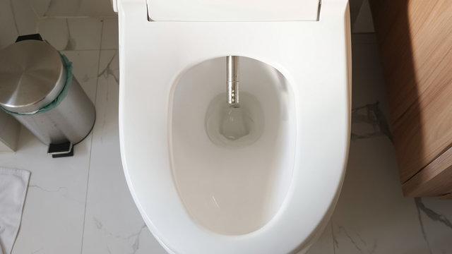modern silver bidet injector appears in white flush near rubbish bin smart home bathroom close upper view