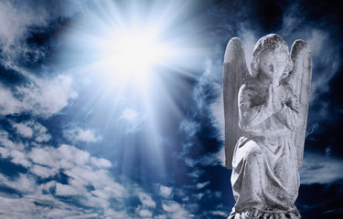 Fotomurales - Ancient statueof angel in rays of light against sky with clouds