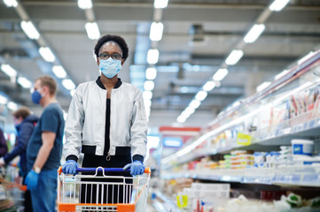 African woman wearing disposable medical mask and gloves shopping in supermarket during coronavirus...