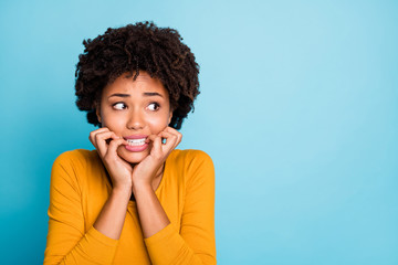 Fototapete - Close up photo of frustrated horrified afro american girl look copyspace fear bite nails teeth wear style stylish trendy pullover isolated over blue color background