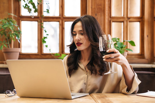Image of serious adult woman drinking red wine and working with laptop