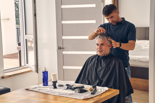 Young handsome man making hairstyle for his client