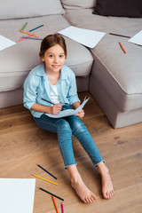 overhead view of happy child sitting on floor and drawing in living room
