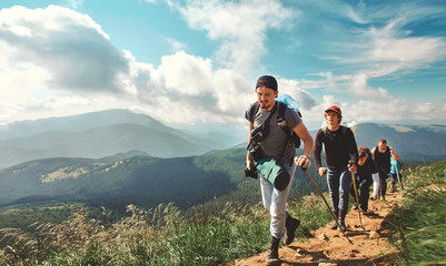 Company of friends travelers walking on the mountain hill with grass field, hiking in mountains, enjoying beautiful scenery. traveling lifestyle, people in nature, wild nature