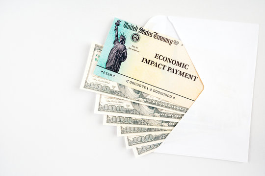 United states treasury check with the text economic impact payment in envelope with 100 dollar bills.