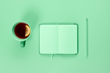 Tea cup and fancy notebook with empty or blank page on desk from above. Copy space