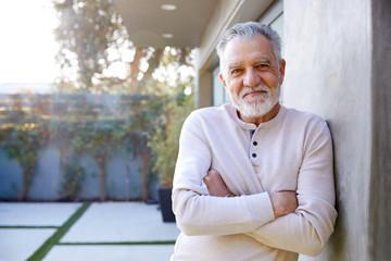 Portrait Of Smiling Retired Senior Hispanic Man In Garden At Home Against Flaring Sun