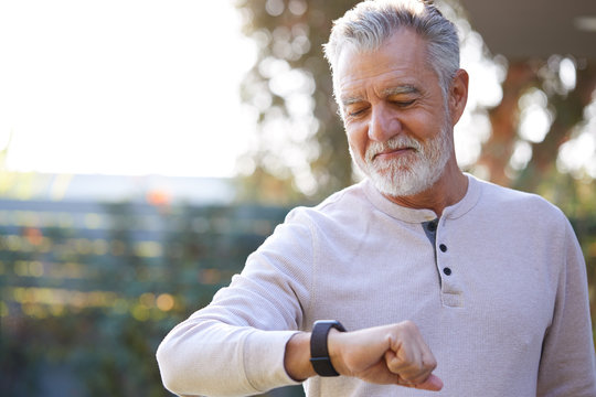 Senior Hispanic Man Checking Health Monitor On Smart Watch In Garden At Home