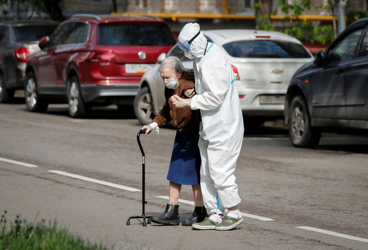 A medical specialist assists an elderly woman to cross a road in Moscow