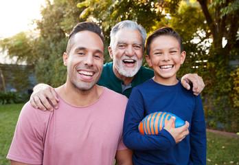 Portrait Of Multi-Generation Male Hispanic Family In Garden Smiling At Camera
