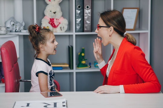 Cute little girl at speech therapist's office. Small child practicing articulation with therapist at private lesson at home