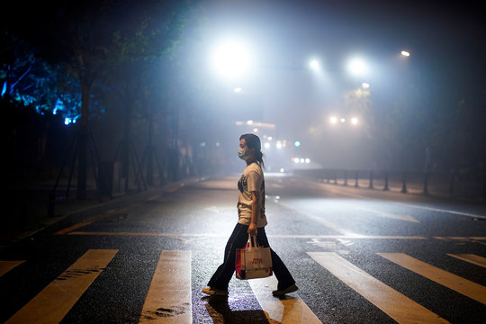A woman wearing a protective mask walks on a street in Wuhan
