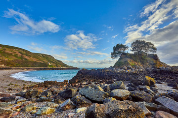 Image of Bouley Bay with beacha and harbour with stones in the foreground. Jersey Channel Islands