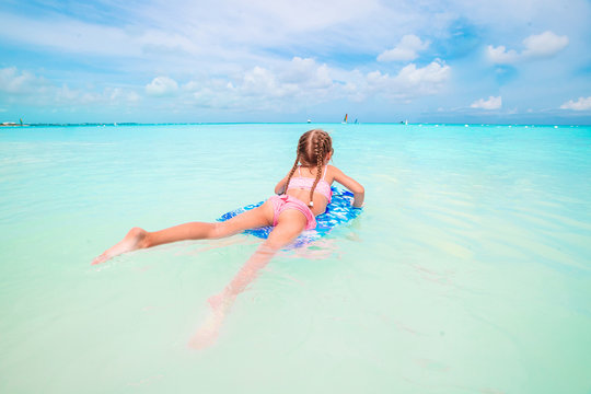 Little girl relaxing on inflatable air mattress in the sea