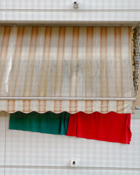 Green and red fabric hanging out to dry at the balcony