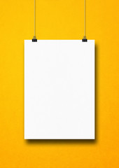 White poster hanging on a yellow wall with clips